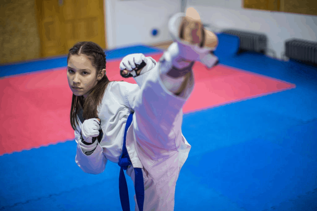 girl doing high kick in Taekwondo