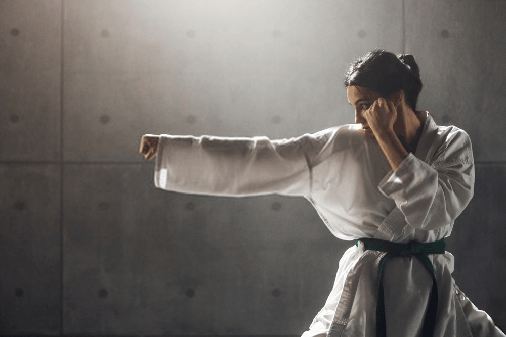 Young woman in kimono practicing karate