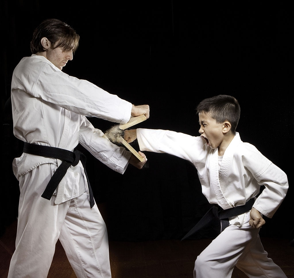 boy in karate class punching and breaking wood