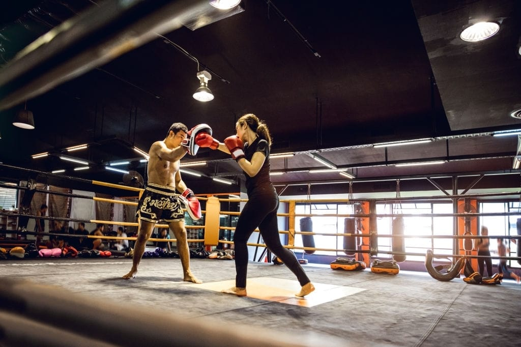 Modern gym facility in Bangkok, young athletes training for a Muay Thai class,