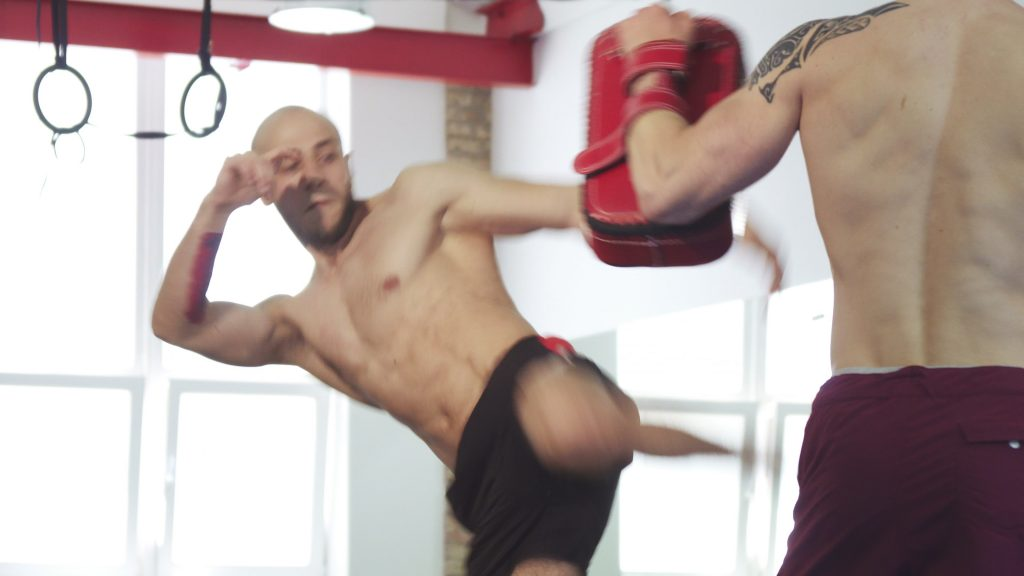 bearded muay thai fighter training with his coach at the gym