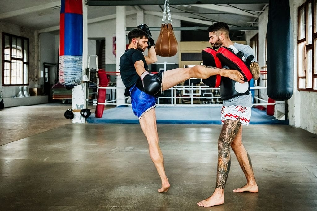 Two muay thai boxing athletes training kicks in an old gym